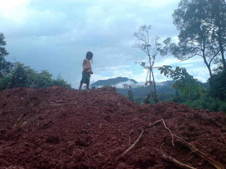 Lao kid playing on a mudslide
