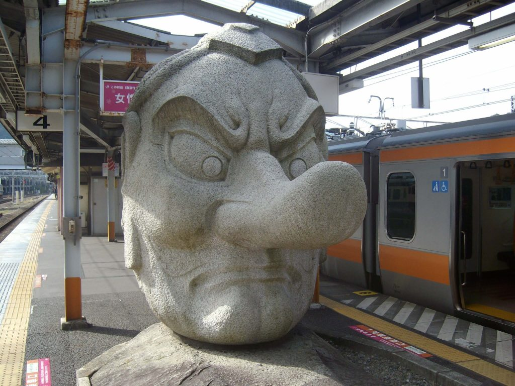 The large tengu head statue on the Takao station platform