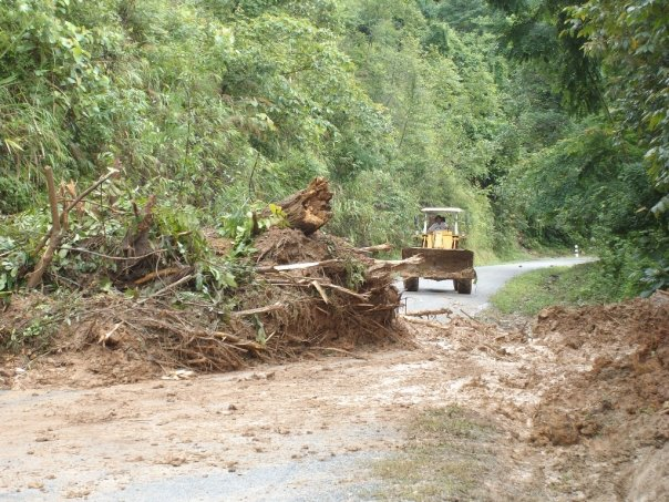 The bulldozer clears a path through the landslide