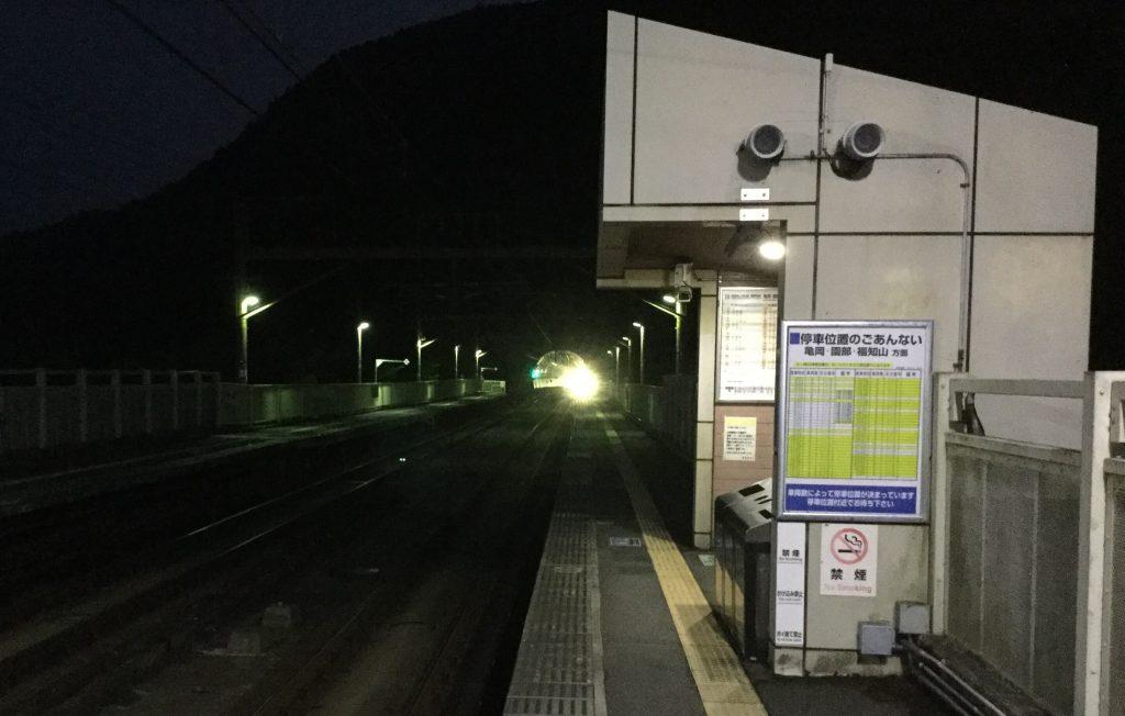 A train approaches Hozukyo Station through the Arashiyama tunnel