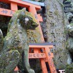Moss-covered fox guardians at Fushimi Inari