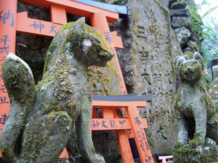 Moss-covered fox guardians at Fushimi Inari