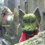 Moss-covered fox statues at Fushimi Inari