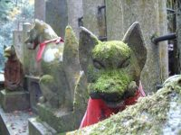 Moss-covered fox statues at Fushimi Inari