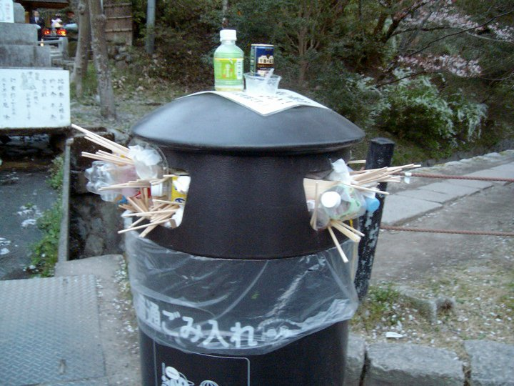 An overstuffed trash can on the Philosopher's Path during cherry blossom season