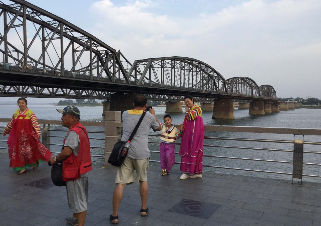 Chinese tourists pose in Korean hanbok with North Korea behind them