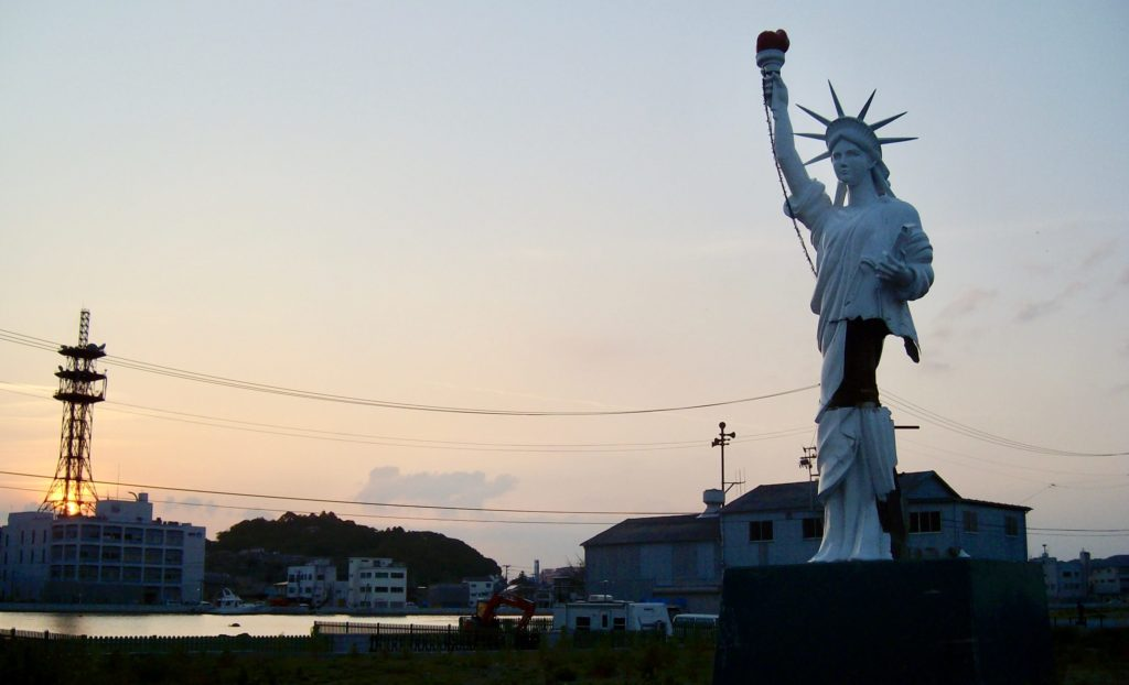 A damaged Statue of Liberty replica which fell off a pachinko parlour and stood temporarily an the island in the river in Ishinomaki