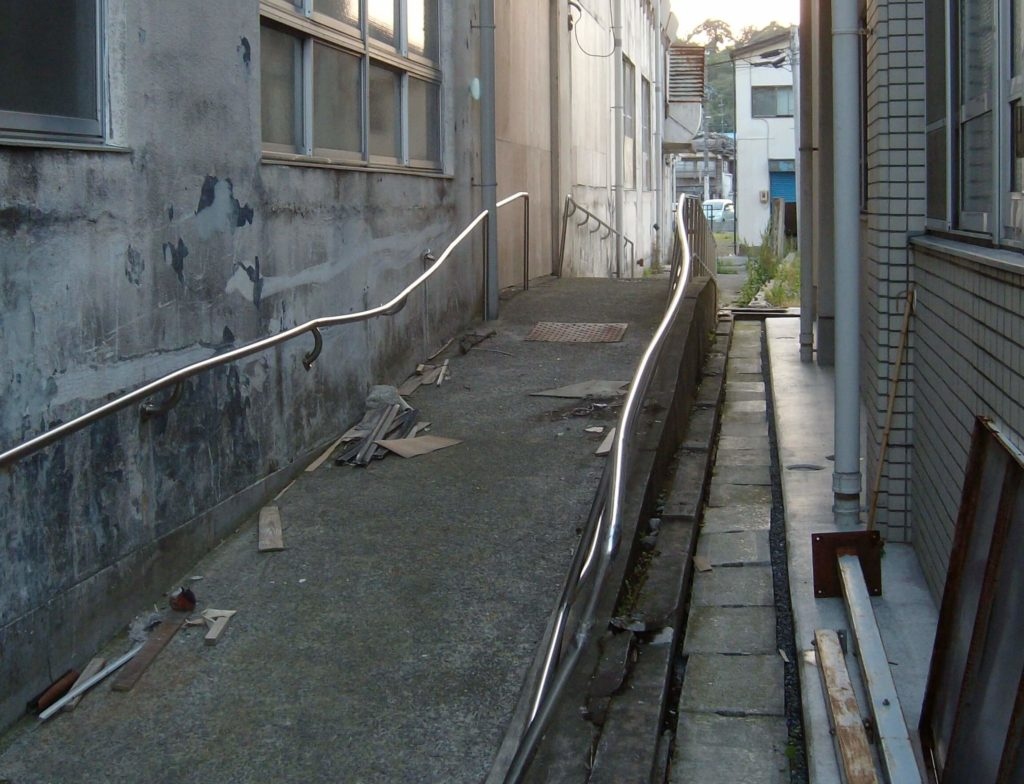 The space between buildings where are a car was previously trapped after the tsunami