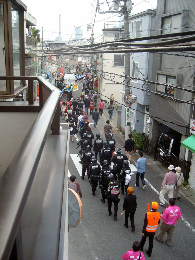 A parade of people in costume passing below my balcony in Tokyo