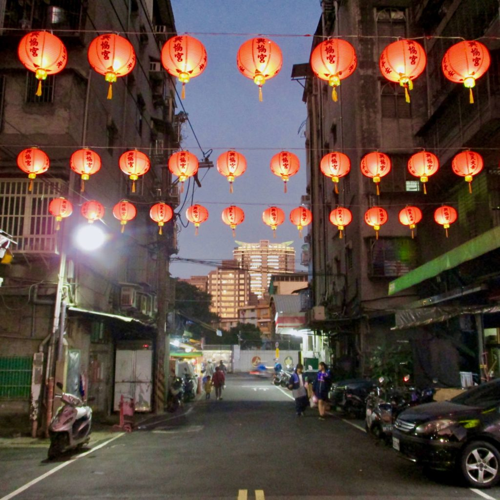 Red temple lanterns suspended above the street in Sanchong, Taipei