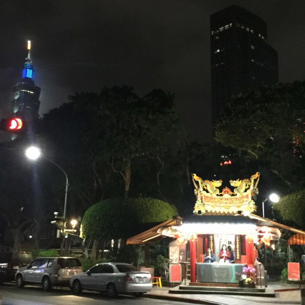 View of Taipei 101 and a small temple in the park